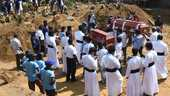 TOPSHOT - Relatives carry coffins of bomb blast victims for a burial ceremony at a cemetery in Negombo on April 24, 2019, three days after a series of suicide attacks targeting churches and luxury hotels in Sri Lanka. (Photo by LAKRUWAN WANNIARACHCHI / AFP) CHURCH AFTERMATH OF THE TERRORISM EXPLOSION Horizontal EASTER religion TOPSHOTS ORG XMIT: 593