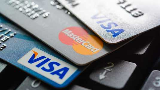 43482502 - group of credit cards on computer keyboard with visa and mastercard brand logos
