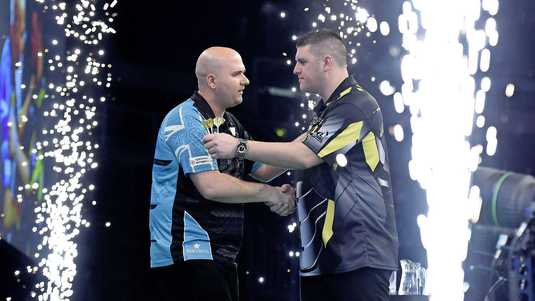Rob Cross (l) wordt door Daryl Gurney gefeliciteerd. De Brit is na tien speelronden de nieuwe koploper in de Premier League.