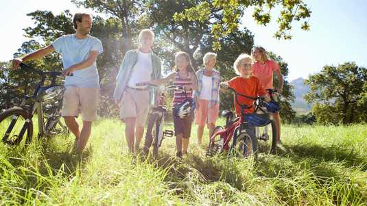 Multi-generation family pushing mountain bikes in rural field
