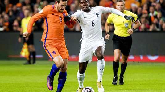 Paul Pogba in duel met Vincent Janssen (l).